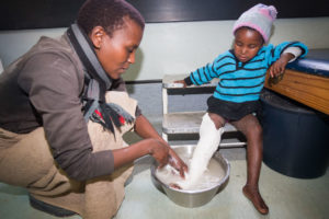 A Mom helps to remove the plaster cast of a child with club foot.